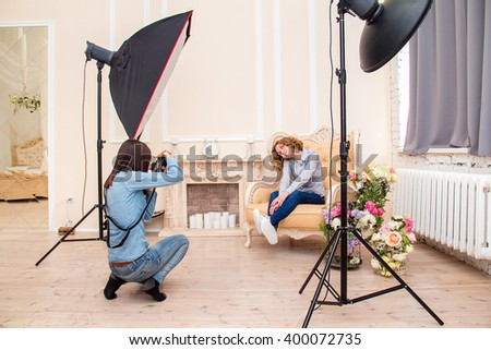 Woman photographer in a studio making portrait photo shoot session for young woman. Softbox flash and other impulse light equipment in the interior of photographic studio #400072735