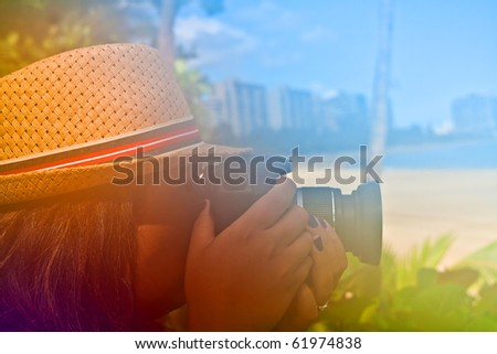 Woman photographer shooting with her digital camera outdoors in a tropical area with abstract color glow.