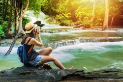woman photographer take photo waterfall in the forest on holiday.