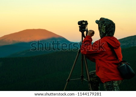 woman photographer takes a picture of a dawn in the mountains by camera on a tripod