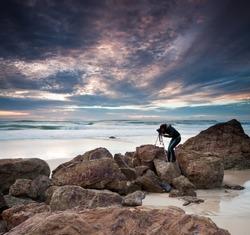 woman photographer takes photo of the beautiful seascape (miami beach, queensland, australia)