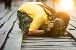 woman photographer taking pictures, shooting from low angle, kneeling  on ground