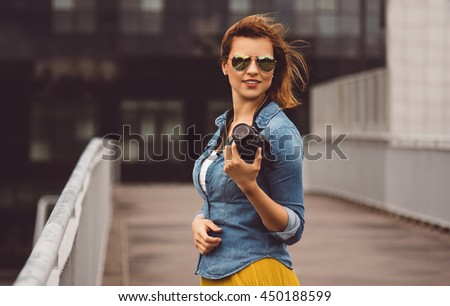 Woman photographer traveling trip photography concept. Red haired woman in casual clothing, jeans holding an amateur digital camera.