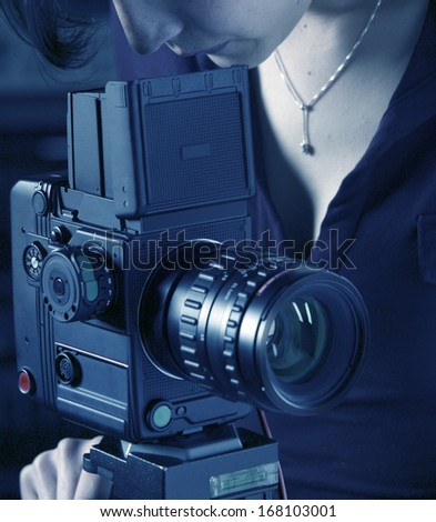 Woman photographer working with medium format camera on a tripod blue tone