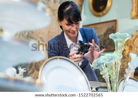 woman photographing antique objects on display