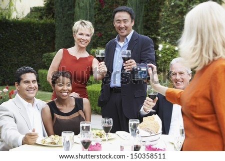 Woman photographing friends while celebrating with food and drink in garden