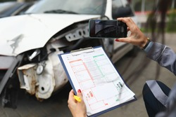 Woman photographs a broken car on smartphone and holds insurance documents in her hands. Damage assessment after car accident concept