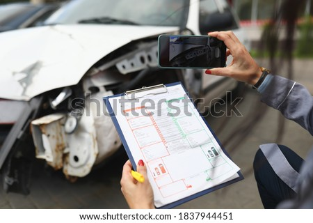 Woman photographs a broken car on smartphone and holds insurance documents in her hands. Damage assessment after car accident concept Foto stock ©