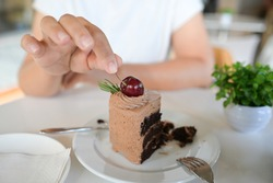 Woman picking cherry fruit decorated on chocolate cake on table