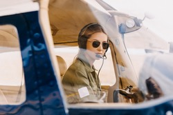 Woman pilot in airplane cockpit, wearing headset and sunglasses.