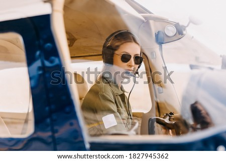 Woman pilot in airplane cockpit, wearing headset and sunglasses. Сток-фото ©