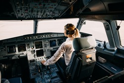 Woman pilot sitting in aircraft cockpit, flying the plane.