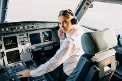 Woman pilot sitting in aircraft cockpit, wearing headset, looking at camera.
