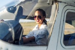 Woman Pilot Sitting in Cabin of Modern Aircraft.