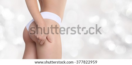 Woman pinches her thigh to control cellulite isolated on blurred light background