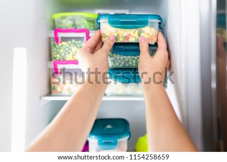 Woman placing container with frozen mixed vegetables in refrigerator. Stockfoto ©