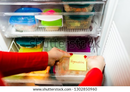 Woman placing container with frozen mixed vegetables in refrigerator. #1302850960