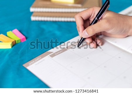 Woman planning agenda and schedule using calendar event planner, Writing plan on memo scheduled, planned to vacation weekend.