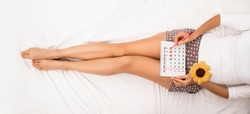 Woman planning her monthly menstruation calendar, mark the days of menstruation and ovulation. She lying on bed wearing home clothes, top view