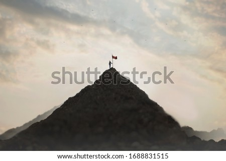 woman plants his flag on the mountain peak as a sign of success Foto stock ©