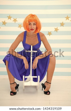 Woman playful cheerful mood having fun. Fun and entertainment. Back to childhood. Girl wig rides swing little horse. Lady red or ginger wig blue dress rides rocking horse. Comic and humorous concept. #1434319109