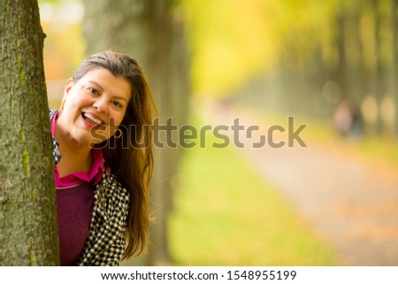 Woman playfully looks to the camera getting her head out of the tree trunk in the park.  #1548955199