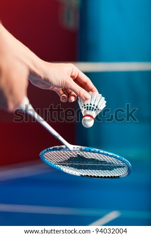 Woman playing Badminton and doing sport in gym, only serve to be seen - stock photo