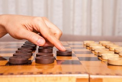 Woman playing  checkers game makes his move.