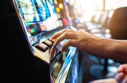 Woman Playing Classic Slot Machine Inside Las Vegas Casino. One Handed Bandit Game Play. Gambling Industry Theme.