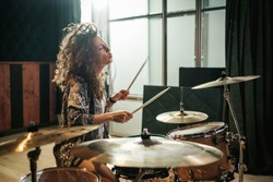Woman playing drums during music band rehearsal