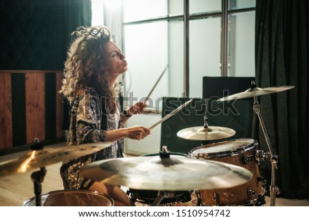 Woman playing drums during music band rehearsal ストックフォト ©
