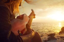 Woman playing guitar on sunset beach