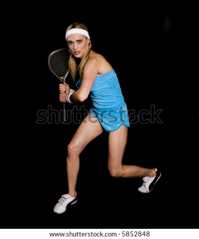 Woman playing racquetball against a black background