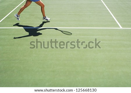 woman playing tennis, only half of her body visible, shadow holding a tennis racket seen on the ground,