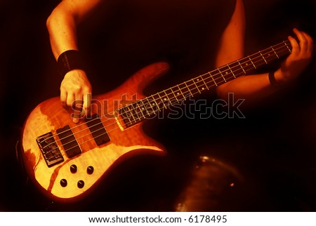 woman playing the guitar in a band isolated on black background