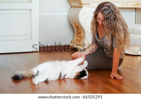 Woman playing with a cat.