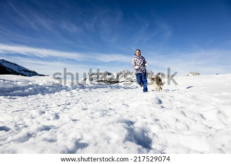 Woman playing with her dog on snowy landscape