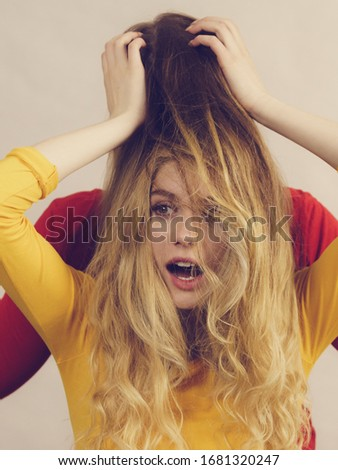 Woman playing with her female friend long ombre color hair. Different hairdo colors, haircare and hairstyling.