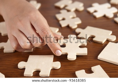 woman playing with jigsaw puzzle pieces