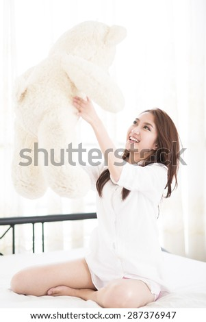 woman playing with teddy bear in the bedroom