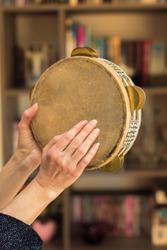 Woman plays traditional tambourine closeup