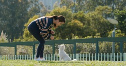 Woman plays with her dog at park