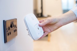 Woman Plugging Smart Plug Into Wall Socket At Home