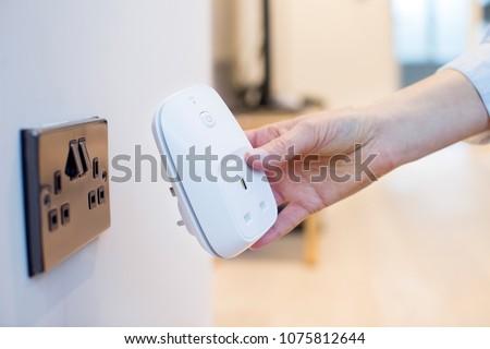 Woman Plugging Smart Plug Into Wall Socket At Home
