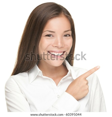 Woman pointing. Closeup portrait of young smiling woman pointing at copy space. Isolated on white background. Asian / Caucasian female model.