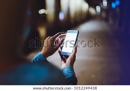 Woman pointing finger on blank screen smartphone on background bokeh light in night atmospheric city, hipster using in hands clean gadget mobile phone closeup, mockup online wifi internet concept