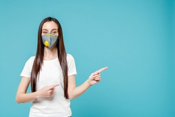 woman pointing fingers at copyspace wearing respirator mask isolated on blue background