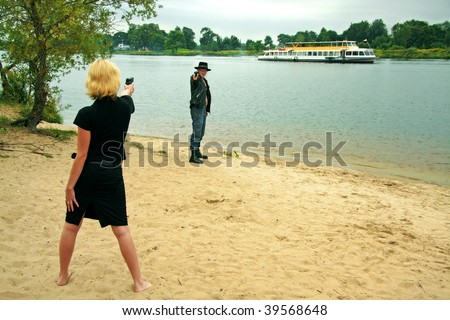 woman pointing gun at man wearing cowboy hat, river and ship in background
