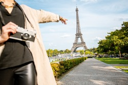 Woman pointing on the famous Eiffel tower traveling in Paris. Cropped image with no face