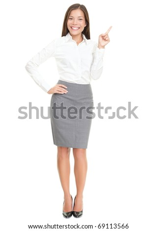 Woman pointing on white standing in full length. Caucasian / Asian woman smiling. Isolated over white background.